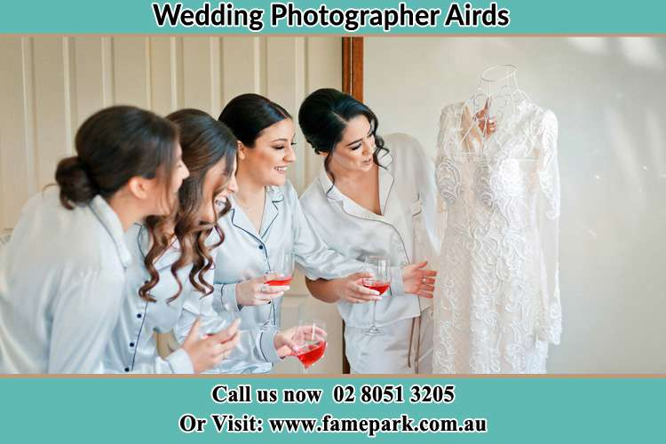 Photo of the Bride and the bridesmaids looking at the wedding gown Airds NSW 2560