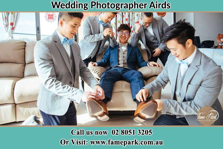 Photo of the Groom helping by the groomsmen getting ready Airds NSW 2560