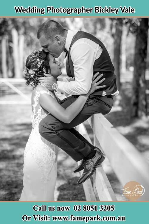 Photo of the Groom sitting on the fence while kissing the Bride on the forehead Bickley Vale NSW 2570
