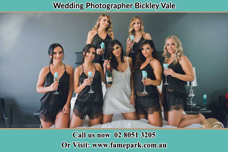 Photo of the Bride and the bridesmaids wearing lingerie and holding glass of wine on bed Bickley Vale NSW 2570