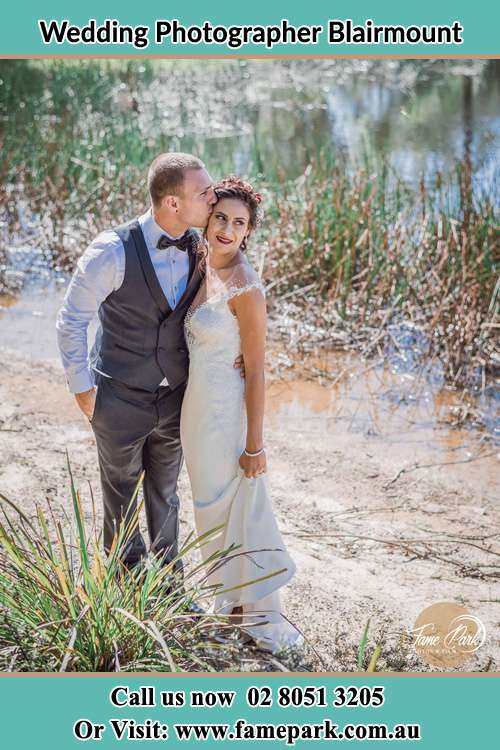 Photo of the Groom kiss the Bride near the lake Blairmount NSW 2559