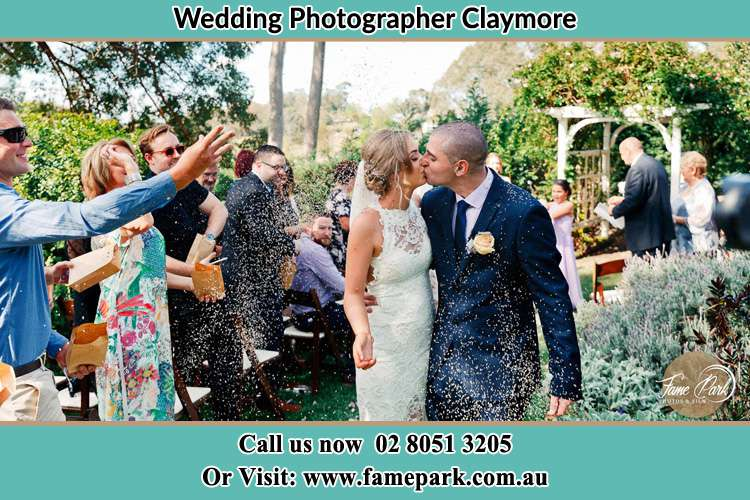 Photo of the Bride and the Groom kissing while showering rice by the visitors Claymore NSW 2559