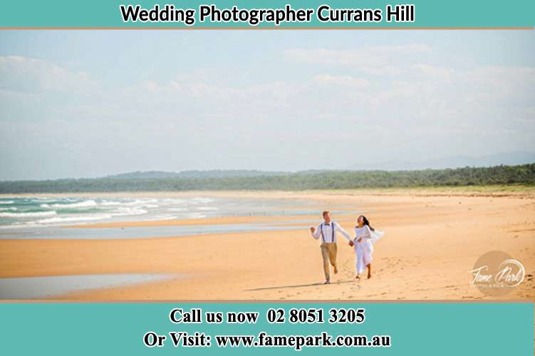 Photo of the Groom and the Bride walking at the sea shore Currans Hill NSW 2567