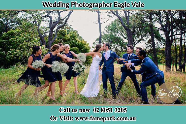 Photo of the Bride and the Groom kissing while teasing by the entourage Eagle Vale NSW 2558