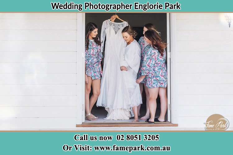 Photo of the Bride and the bridesmaids checking the wedding gown at the front door Englorie Park NSW 2560