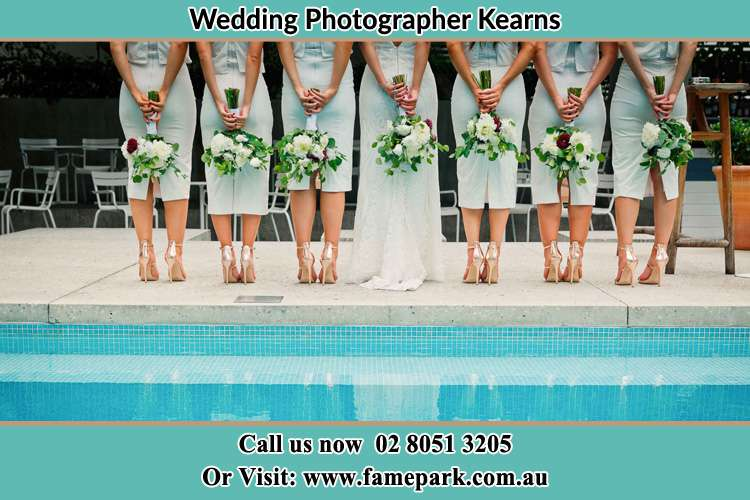 Behind photo of the Bride and the bridesmaids holding flowers near the pool Kearns NSW 2558