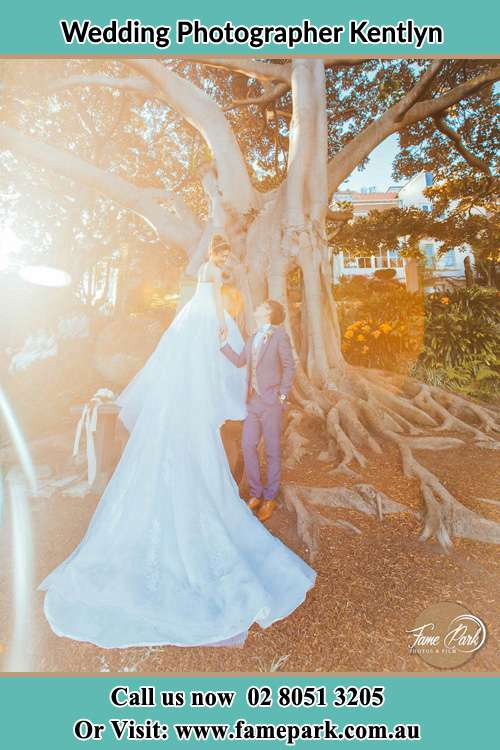 Photo of the Bride and the Groom looking each other besides the tree Kentlyn NSW 2560