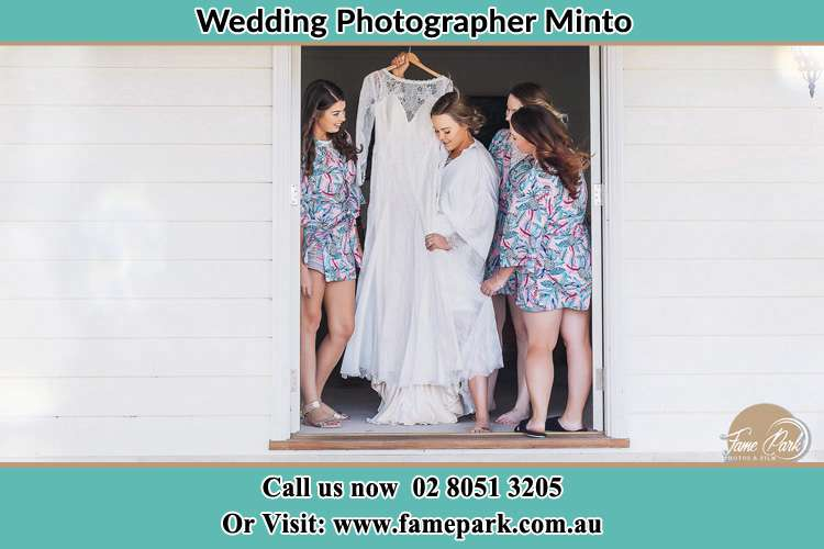 Photo of the Bride and the bridesmaids checking the wedding gown at the front door Minto NSW 2566