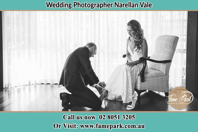 The Bride is being helped by the Groom trying to put on her shoes Narellan Vale NSW 2567