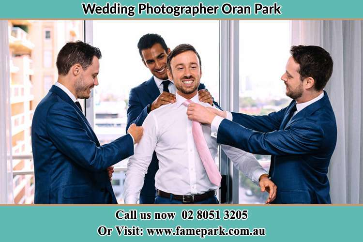 Photo of the Groom helping by the groomsmen getting ready Oran Park NSW 2570