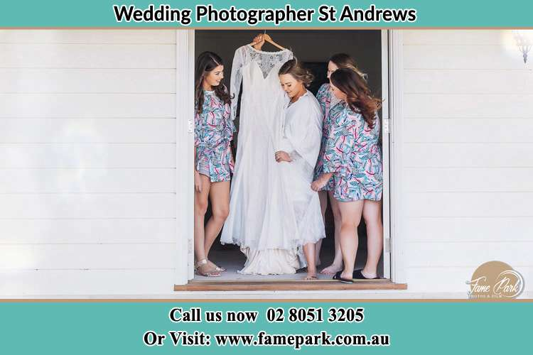 Photo of the Bride and the bridesmaids checking the wedding gown at the front door St Andrews NSW 2566