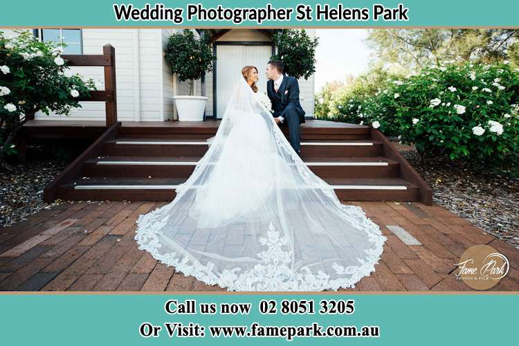 Photo of the Bride and the Groom looking each other while sitting at the staircase St Helens Park NSW 2560